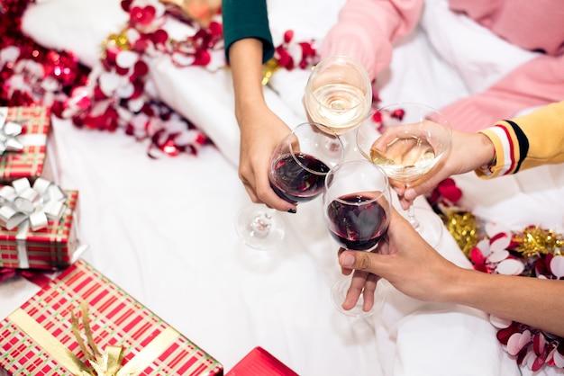 Mãos, de, pessoas comemorando, ano novo partido, em, lar, com, vinho bebendo vidro