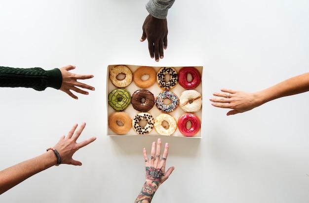 Mãos de pessoas de diversidade atingem por donuts
