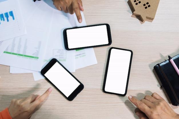 Mãos de pessoas de negócios usando a tela branca de telefone inteligente na vista superior