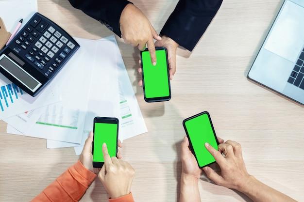 Mãos de pessoas de negócios usando a tela verde do telefone inteligente na vista superior.