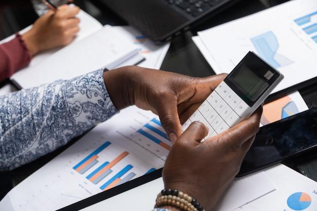 Mãos de pessoas de pele escura seguram a calculadora contra documentos financeiros no espaço de negócios