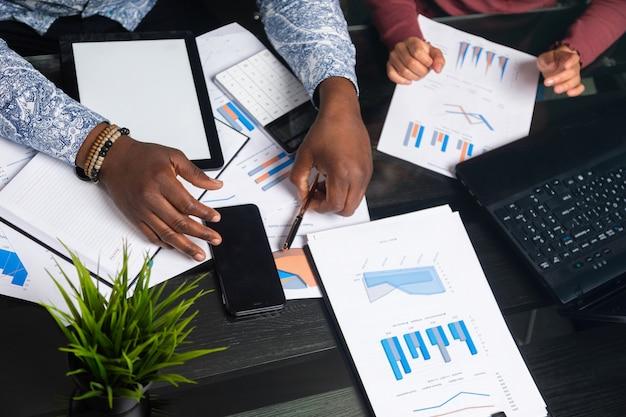 Mãos de pessoas de pele escura trabalham com tablet de documentos financeiros no espaço de negócios closeup