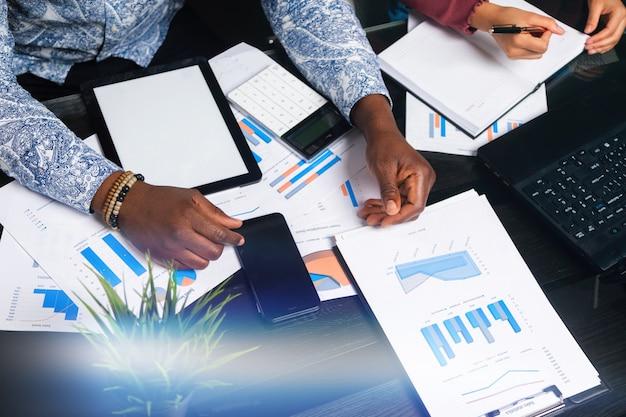 Mãos de pessoas de pele escura trabalham com tablet em fundo de documentos financeiros no espaço de negócios