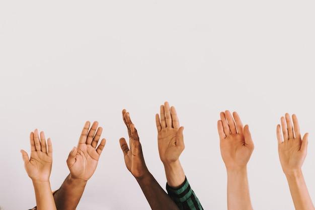 Mãos de pessoas levantadas de diferentes nacionalidades
