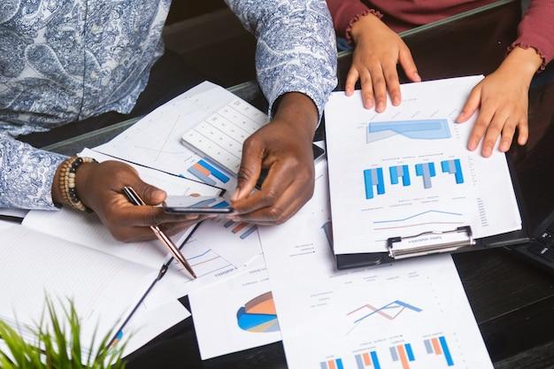 Mãos de pessoas negras, segurando o telefone móvel, documentos financeiros em close-up do espaço de negócios