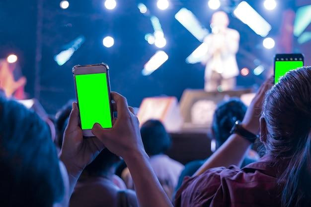 Mãos de pessoas segurando o telefone móvel esperto com gravação de tela verde e tirar uma foto no concerto de música