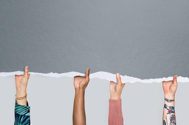 Mãos de pessoas segurando um fundo de papel rasgado cinza com espaço de cópia