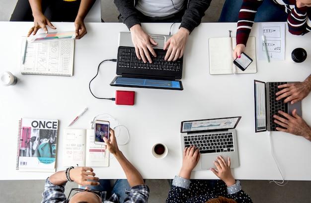 Mãos de pessoas trabalhando usando laptop na mesa branca