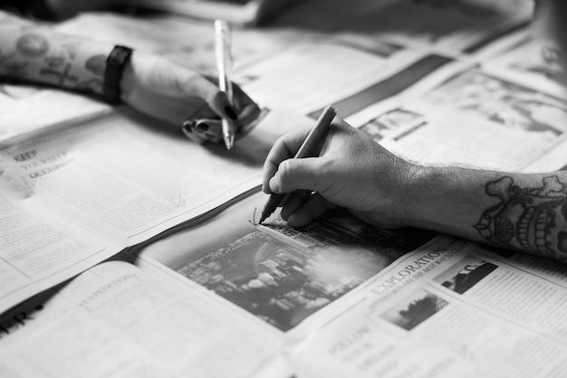 Mãos de pessoas, verificando o trabalho de jornal