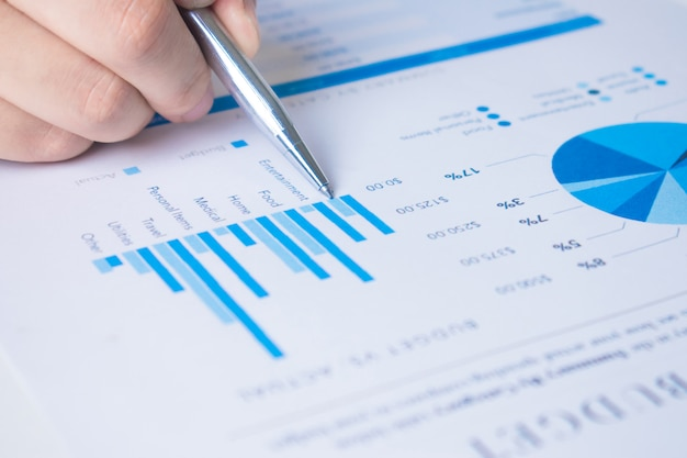 Mãos de profissionais de negócios, use a caneta para apontar para o gráfico e explicar alguns números.