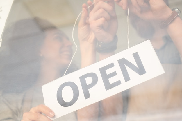 Mãos de proprietários de café, restaurante ou loja pendurando avisos anunciando a abertura na porta de vidro no primeiro dia de trabalho