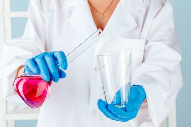 Mãos de químico segurando tubos de ensaio com líquidos e fazendo experimentos