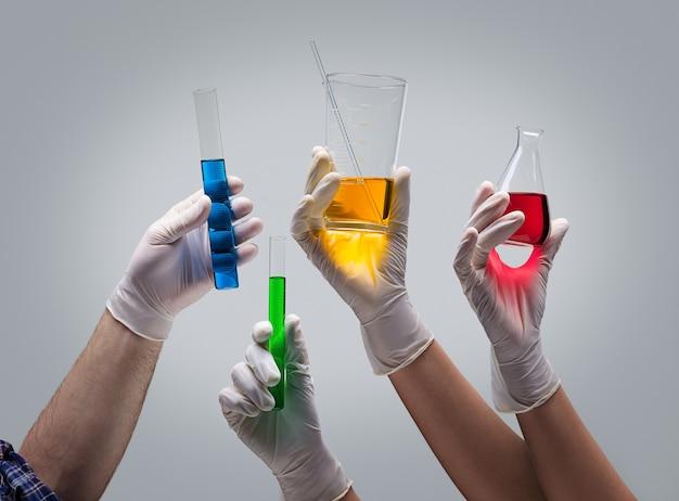 Mãos de químico segurando vidraria de laboratório com líquidos