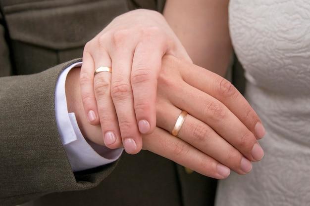 Mãos de recém casado com anéis de ouro nos dedos