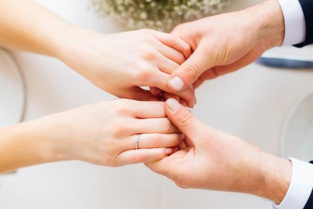 Mãos de recém-casados, a noiva e o noivo estão de mãos dadas e sentados à mesa de um restaurante