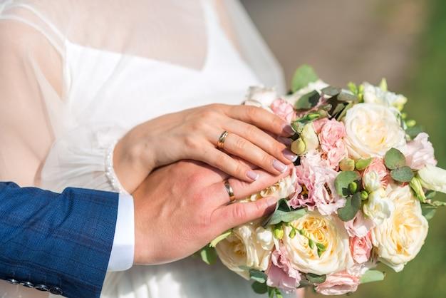 Mãos de recém-casados com anéis. buquê de casamento no fundo das mãos da noiva e do noivo com um anel de ouro