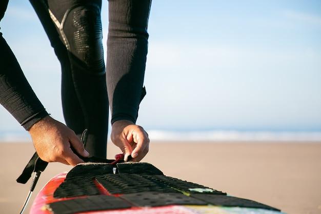 Mãos de surfista com roupa de neoprene amarrando a prancha de surfe ao tornozelo na praia