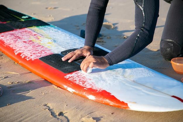 Mãos de surfista com roupa de neoprene encerando a prancha de surf na areia na praia do oceano