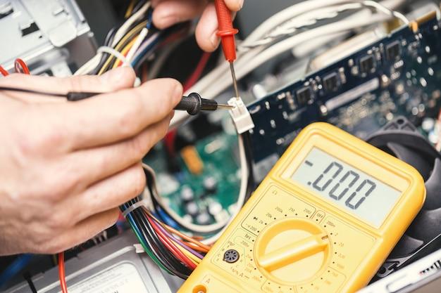 Mãos de técnico com voltímetro acima da placa-mãe do computador.