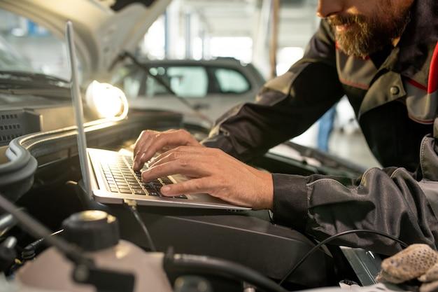 Mãos de trabalhador do sexo masculino de meia-idade do serviço de manutenção de automóveis, curvando-se sobre o compartimento do motor aberto na oficina, enquanto usa o laptop