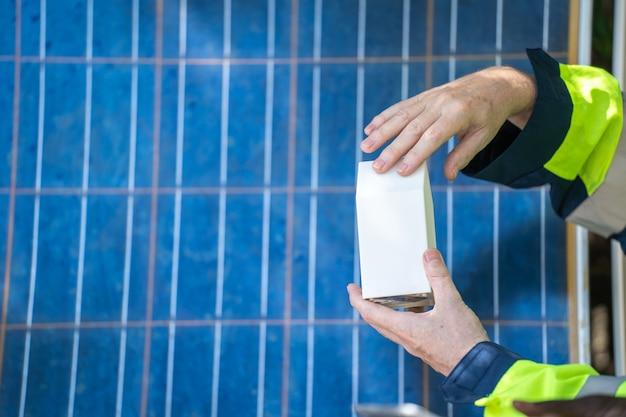 Mãos de trabalhador mostrando e verificando o edifício do modelo e o painel de célula solar para tecnologia sustentável.