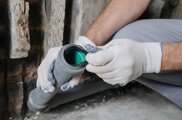 Mãos de trabalhadores estão instalando canos de esgoto na cozinha de um apartamento.