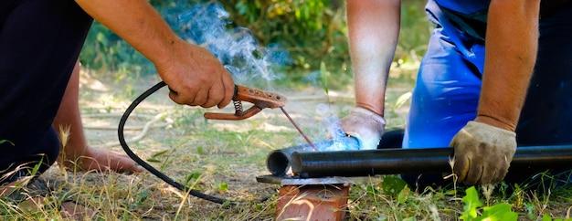 Mãos de trabalhadores soldando tubos de metal com soldagem a arco elétrico