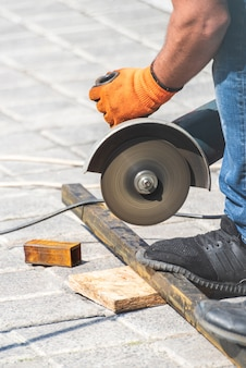 Mãos de trabalho corta um tubo de metal com rebarbadora