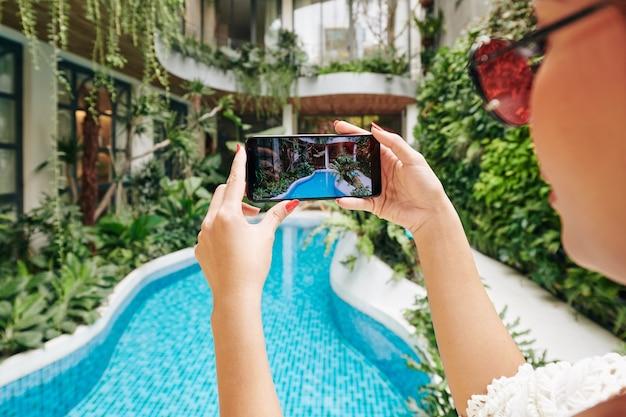 Mãos de turista tirando foto de piscina em resort spa luxuoso em smartphone para postar nas redes sociais