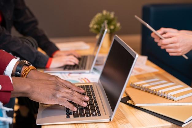 Mãos de um africano pressionando as teclas do teclado do laptop enquanto se prepara para um seminário ou conferência entre colegas de grupo