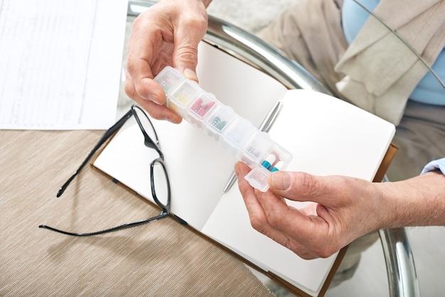 Mãos de um aposentado segurando um recipiente de plástico para comprimidos sobre um caderno aberto e óculos na mesa enquanto vai tomar remédio