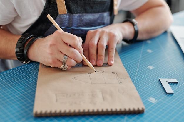 Mãos de um artesão contemporâneo com lápis sobre o bloco de notas fazendo o esboço de um item de couro enquanto está sentado à mesa