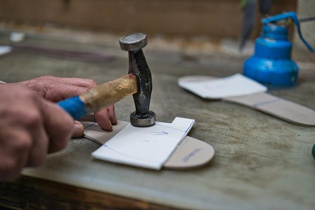 Mãos de um artesão ortopédico furando com a ajuda de um martelo de madeira azul alguns modelos de espuma e borracha artesanal e personificados para os pés. barco de cauda azul na parte inferior da bancada.