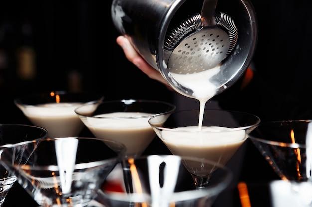 Mãos de um barman segurando uma coqueteleira servindo uma bebida em uma taça de martini.