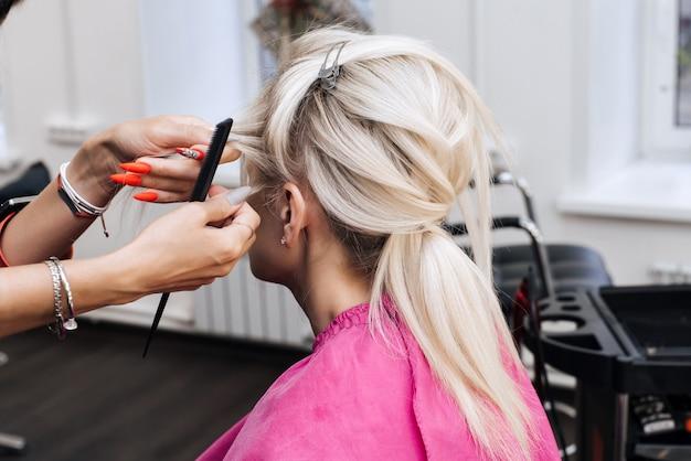 Mãos de um cabeleireiro profissional fazem um penteado para uma garota loira de cabelos longos em um salão de beleza