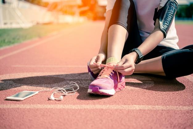 Mãos de um cadarço jovem e tênis rosa em uma pista de jogging de manhã para exercer