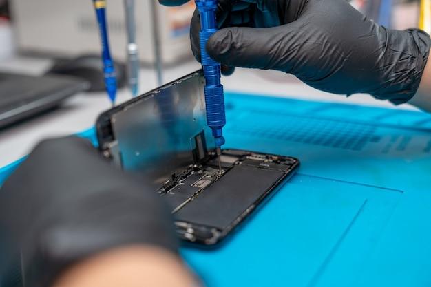 Mãos de um capataz consertando um smartphone com uma chave de fenda