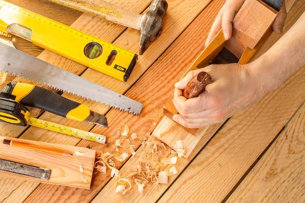 Mãos de um carpinteiro aplainado madeira, local de trabalho