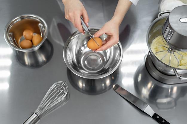 Mãos de um chef pasteleiro quebram um ovo com uma faca em uma cozinha profissional.