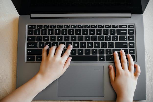 Mãos de um close de criança no teclado do laptop. ensino à distância. ficar em casa.