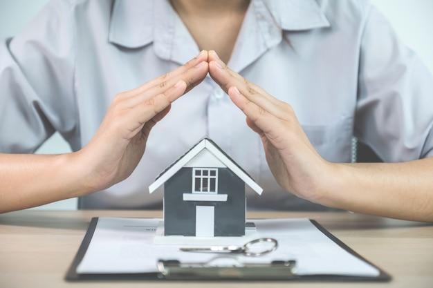 Mãos de um corretor de imóveis impedem o modelo residencial e explicam o contrato de negócios