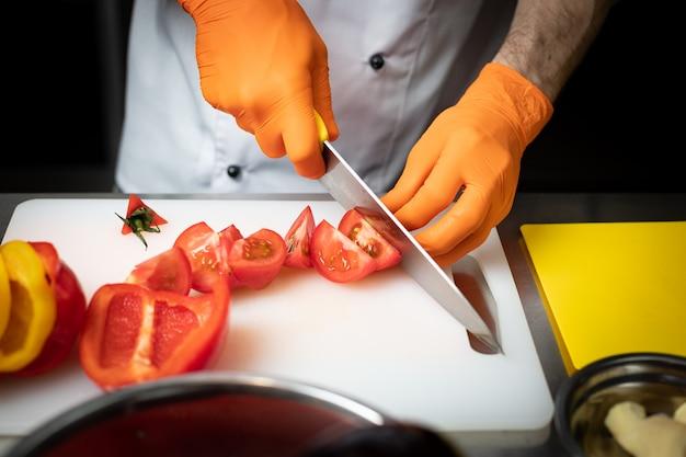 Mãos de um cozinheiro em luvas, fatias de tomates em uma tábua branca, na cozinha