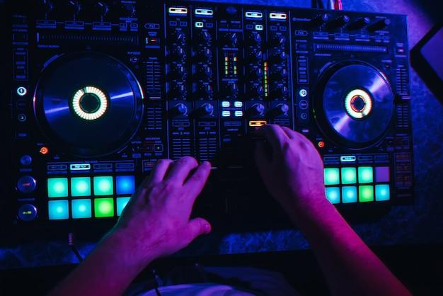 Mãos de um dj em uma cabine tocando no mixer