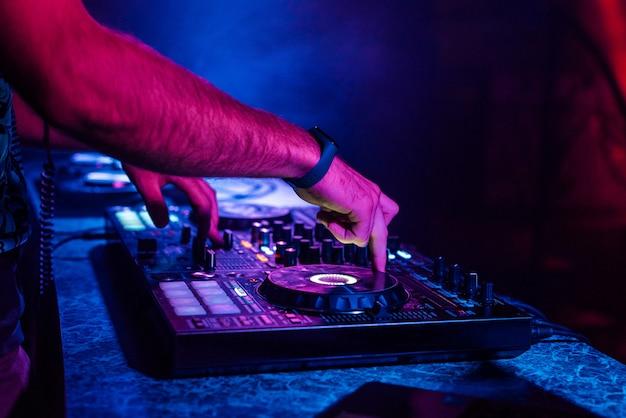 Mãos de um dj tocando música em um mixer em um concerto