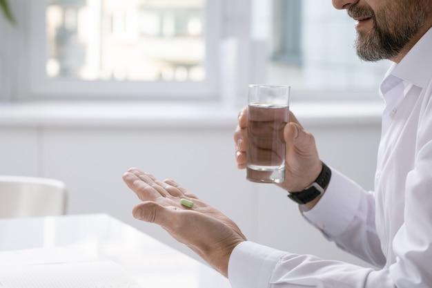 Mãos de um empresário barbudo segurando a pílula enquanto vai pegá-la e um copo d'água sobre a mesa no trabalho