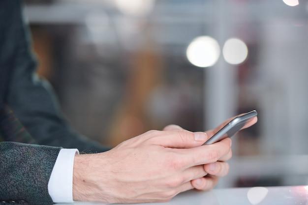 Mãos de um empresário móvel segurando um smartphone e percorrendo informações ou mensagens