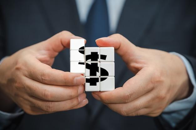 Mãos de um empresário segurando um cubo com um ícone de indicação de dólar visível.