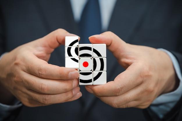 Mãos de um empresário segurando um cubo com um ícone de objetivo de negócios visível.