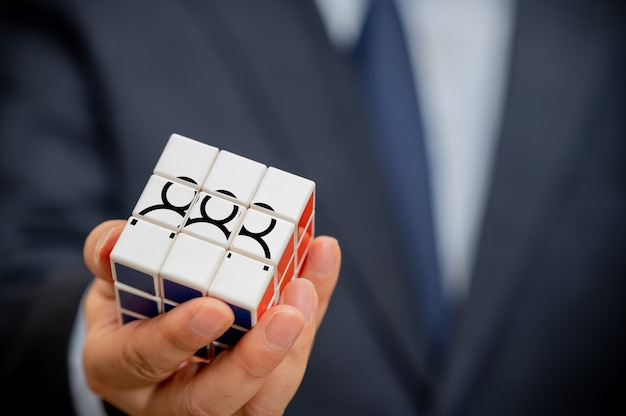 Mãos de um empresário segurando um cubo com um ícone de pessoas visível.