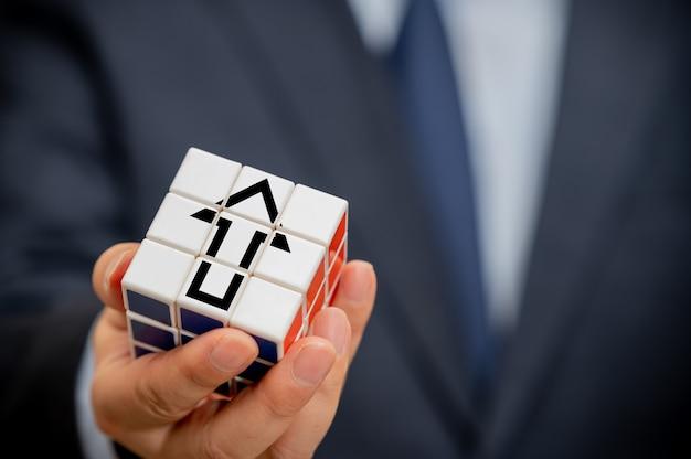 Mãos de um empresário segurando um cubo com um ícone de seta visível.